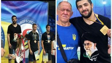 Photo of Ukrainian wrestler standing on champion's podium with an image of Supreme Leader on his T-Shirt